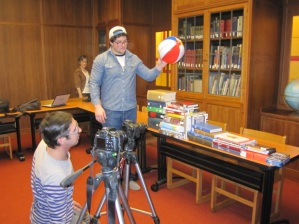 Prof. Steven Coy (left) and student Jared Patterson film the WorldShare sequence with librarian Gretchen Weiner looking on in the background.